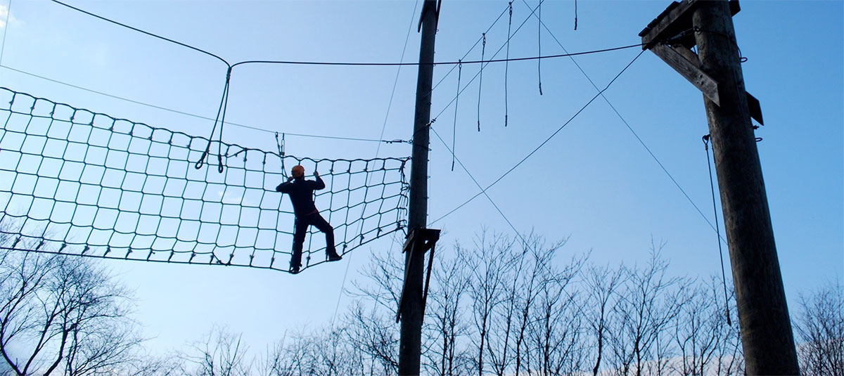 Man on an aerial rope course at Potomac Pathways drug rehab treatment facility