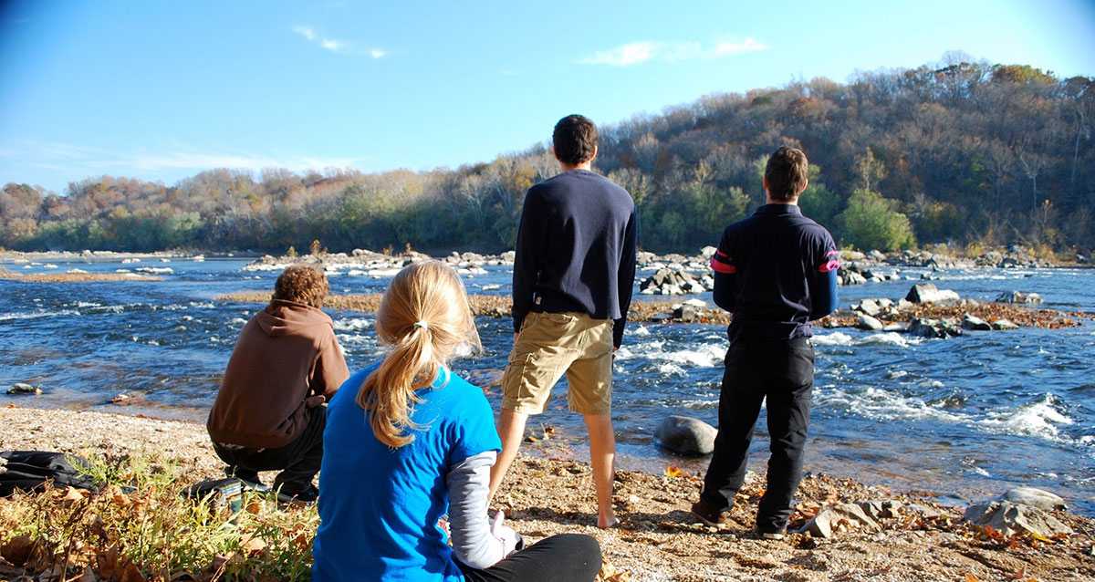Four young people standing on the shore of the Potomac River